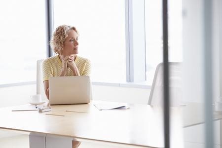 ejecutivo en oficina: Empresaria mayor que trabaja en la computadora portátil en la sala de reunión Mesa Foto de archivo