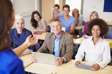 Mature Students In Further Education Class With Teacher