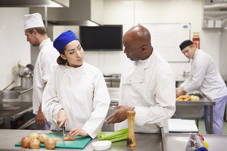 catering food: Teacher Helping Students Training To Work In Catering
