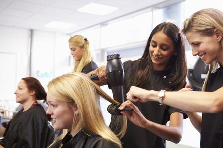 secador de pelo: Ayuda del profesor de formaci�n los estudiantes a convertirse Peluquer�as Foto de archivo