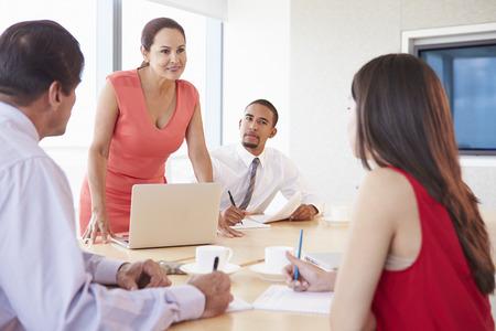 chairman: Four Hispanic Businesspeople Having Meeting In Boardroom