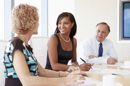 teamwork business: Three Businesspeople Having Meeting In Boardroom