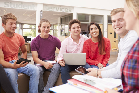 collaborating: Group Of College Students Sitting And Talking Together