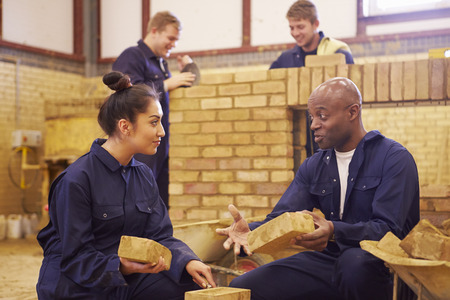 Teacher Helping Students Training To Be Builders Reklamní fotografie - 42314544