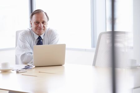 Senior Businessman Working On Laptop At Boardroom Table Stock Photo