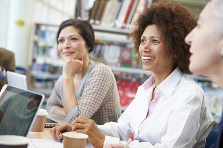 Skupina dospělých osob spolupracují na projektu v knihovně