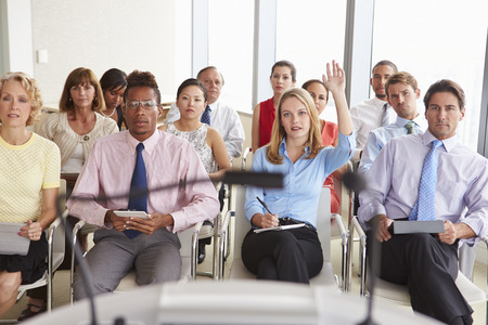 questions: Delegate Asking Question At Business Conference Stock Photo