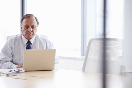 executive chair: Senior Businessman Working On Laptop At Boardroom Table