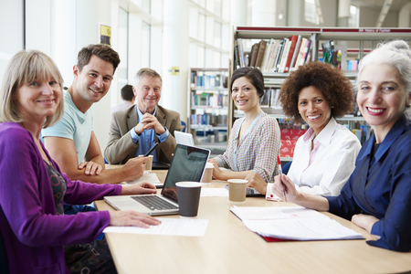Group Of Mature Students Collaborating On Project In Library