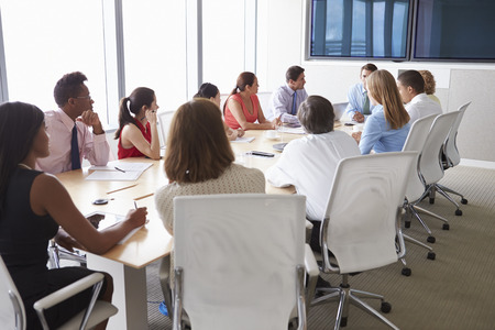 boardroom: Group Of Businesspeople Meeting Around Boardroom Table Stock Photo