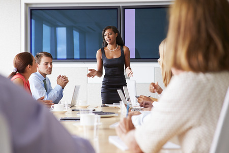african business man: Group Of Businesspeople Meeting Around Boardroom Table Stock Photo