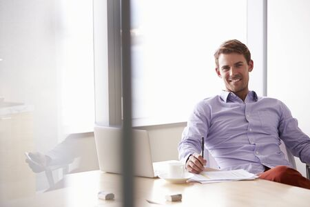 casually dressed: Portrait Of Casually Dressed Businessman Sitting At Desk Stock Photo
