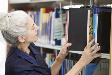 student studying: Female Mature Student Studying In Library Stock Photo