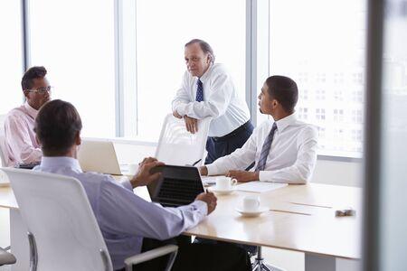 table boardroom: Four Businessmen Having Meeting Around Boardroom Table