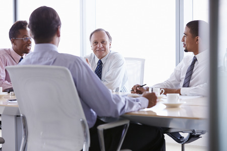 Four Businessmen Having Meeting Around Boardroom Table