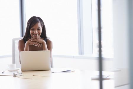 Geschäftsfrau auf Laptop am Sitzungssaaltisch Standard-Bild