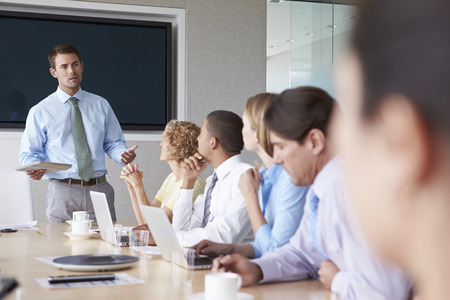 multi cultural: Group Of Businesspeople Meeting Around Boardroom Table Stock Photo
