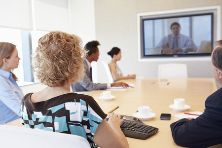 Group Of Businesspeople Having Video Conference In Boardroom