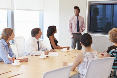 addressing: Businessman By Screen Addressing Boardroom Meeting