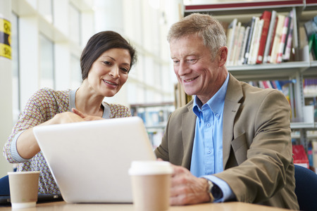helping: Teacher Helping Mature Student With Studies In Library