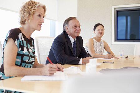 reuniones empresariales: Tres empresarios que tienen reunión en la sala de reunión