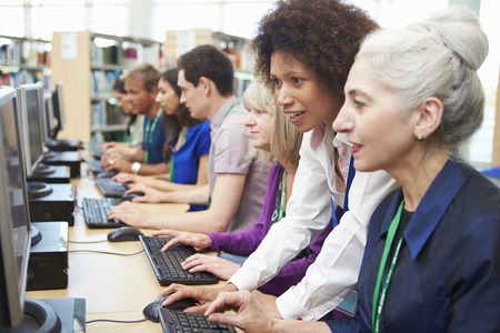 adult student: Group Of Mature Students Working At Computers With Tutor