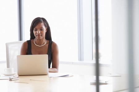 mujeres negras: Empresaria que trabaja en la computadora portátil en la sala de reunión Mesa Foto de archivo