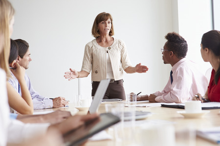 asian businesswoman: Group Of Businesspeople Meeting Around Boardroom Table Stock Photo