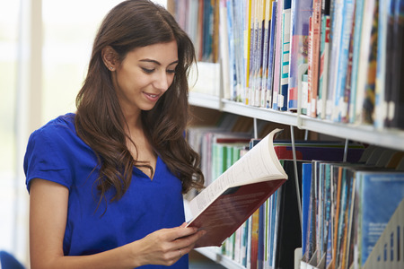 research study: Female University Student Studying In Library