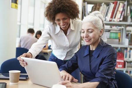 erwachsene: Lehrer helfen Älterer Student Studien in der Bibliothek Lizenzfreie Bilder