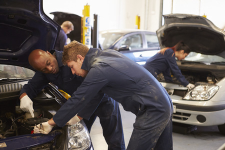 capacitaci�n: Ayuda del profesor de Formaci�n estudiante sea mec�nicos de coche Foto de archivo