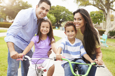 hispanic people: Parents Teaching Children To Ride Bikes In Park