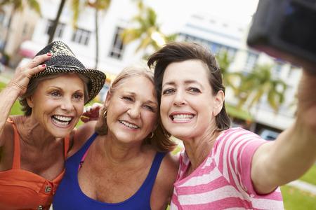 tercera edad: Tres amigos femeninos mayor que toma selfie En el Parque