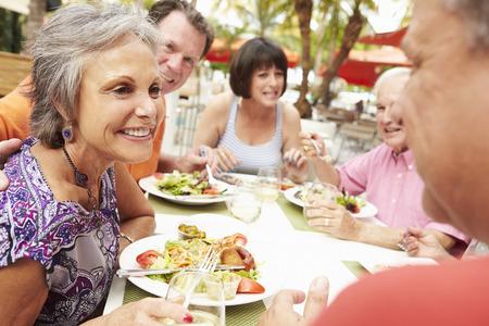 seniors: Grupo de amigos mayores que disfrutan de la comida en restaurante al aire libre
