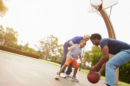 familias felices: Abuelo con el hijo y nieto que juega a baloncesto