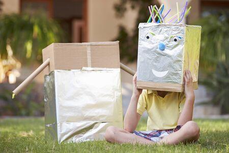 robot: Chłopiec stojący w ogrodzie z Homemade Robot