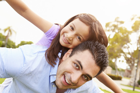 having fun: Father Giving Daughter Piggyback Ride In Garden