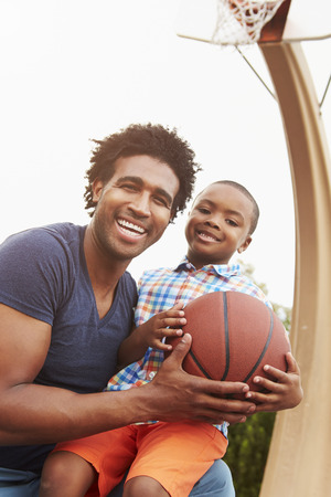outdoor basketball court: Portrait Of Father And Son On Basketball Court