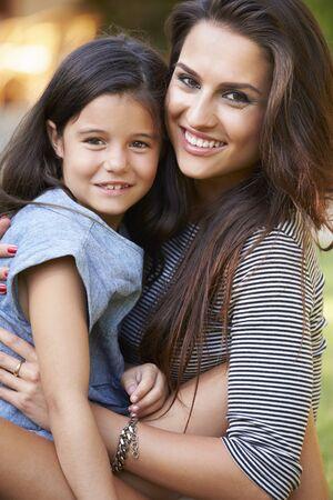 mama e hijo: Retrato de la madre cari�osa y de la hija en el jard�n