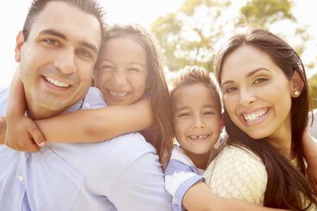 家庭: 父母給孩子背著在花園
