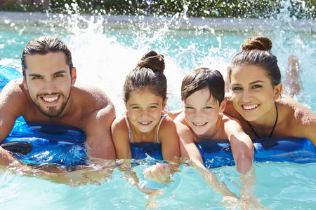 vacation: Portrait Of Family On Airbed In Swimming Pool