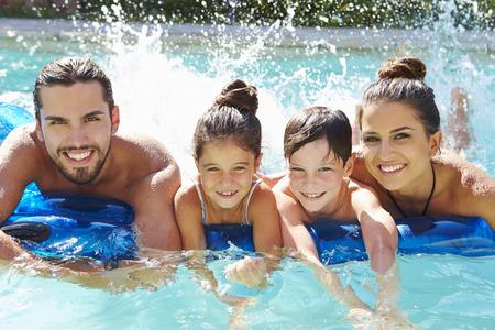 familias felices: Retrato de la familia en cama de aire en piscina