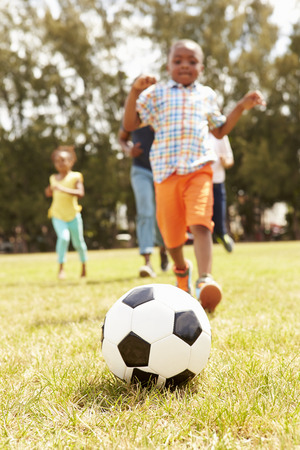 Family Playing Soccer In Park Together 写真素材