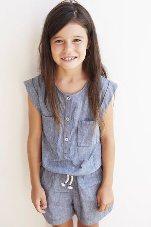 7 years old: Smiling Young Girl Standing Outdoors Against White Wall