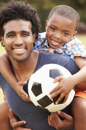 father and child: Father With Son Playing Soccer In Park Together