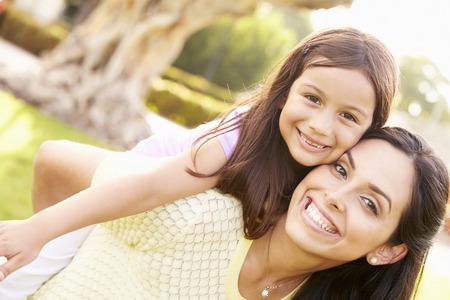 mama e hija: Retrato de la madre hispana e hija en parque