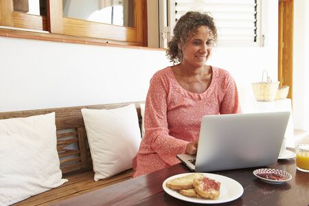 one person: Mature Woman Sitting At Breakfast Table Using Laptop