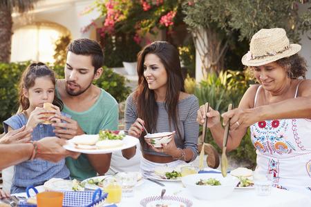 familias felices: Multi generacional Comer comida en el Aire libre Juntos Foto de archivo