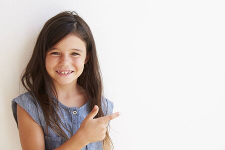 white wall: Smiling Young Girl Standing Outdoors Against White Wall