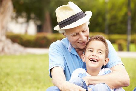 abuelo: Abuelo y nieto que se sientan en parque Juntos Foto de archivo